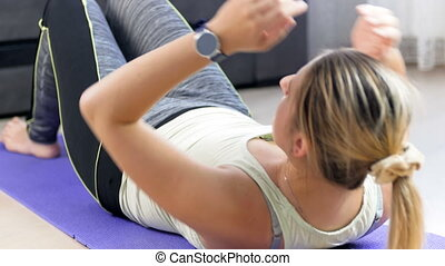 4k video of young woman lying on fitness mat using smart watch to measure her body parameters before doing abdomen crunches