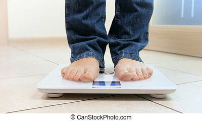 4k footage of young woman stepping on electronic scales and checking her weight