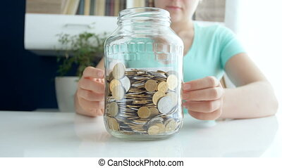 4k video of young woman sticking title Savings on glass jar...