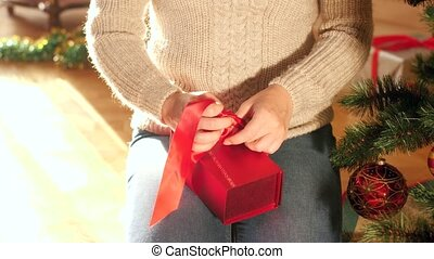 4k video of young woman tying red ribbon bow on box with ...