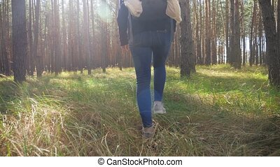 4k footage of young woman with backpack walking in forest and stepping over tall grass on meadow