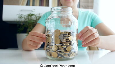 4k video of young woman writing SAvings on glass jar full of...