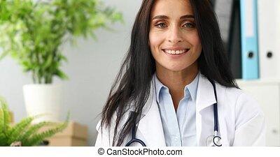 4k video smiling female doctor aganist hospital office...