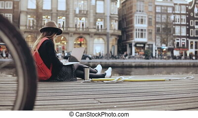 4K Young creative girl sits with laptop outside. Fashion art...