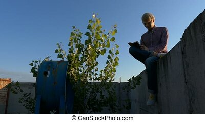Young poet makes notes at sunset on the top of the building....