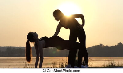 4k - Young Pregnant Girl Does Yoga Bridge With The Trainer Nearby at Sunset
