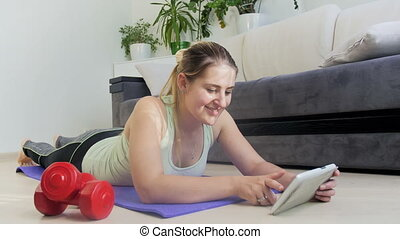 4k zooming in footage of young woman using digital tablet while exercising on fitness mat at home