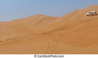 4WD car driving over dunes in oman