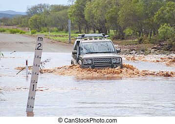 4x4 is slowly crossing flooded road next to a mark indecating waterlevel. Captured during rain season in Western Australia