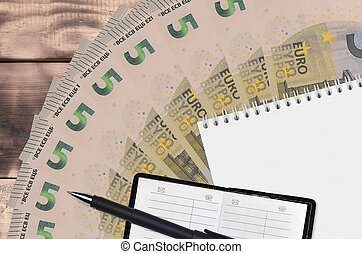 5 euro bills fan and notepad with contact book and black pen. Concept of financial planning and business strategy