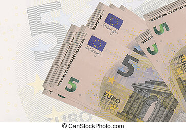 5 euro bills lies in stack on background of big semi-transparent banknote. Abstract presentation of national currency