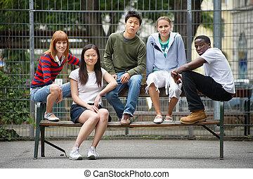 5 friends of different background sitting on a bank - 5 Freund von unterschiedlicher Herkunft sitzen auf einer Bank