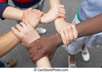 5 hands of young intercultural people holding each other