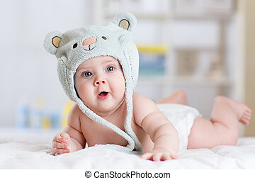 5 months baby girl weared in funny hat lying down on a blanket