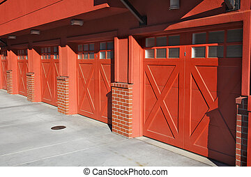 Five red garage doors in perspective as part of an apartment complex
