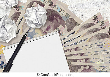 5 Turkish lira bills and balls of crumpled paper with notepad. Bad ideas or less of inspiration concept. Searching ideas for investment