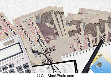 5 Turkish lira bills and calculator with glasses and pen. Tax payment season concept or investment solutions. Financial planning or accountant paperwork