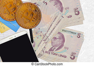5 Turkish lira bills and golden bitcoins with smartphone and credit cards. Cryptocurrency investment concept. Crypto mining or trading transactions