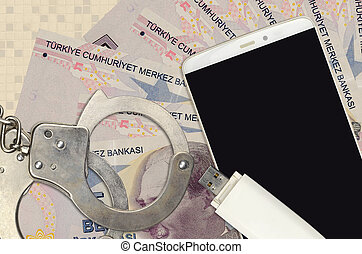 5 Turkish lira bills and smartphone with police handcuffs. Concept of hackers phishing attacks, illegal scam or online spyware soft distribution