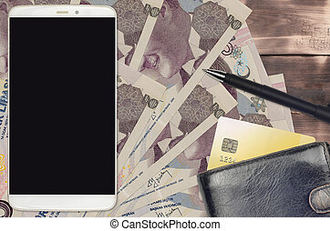5 Turkish lira bills and smartphone with purse and credit card. E-payments or e-commerce concept. Online shopping and business with portable devices usage