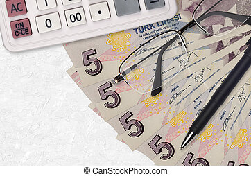 5 Turkish lira bills fan and calculator with glasses and pen. Business loan or tax payment season concept. Financial planning