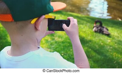 5 year old boy photographed on a mobile phone black swan sitting on the grass near the pond