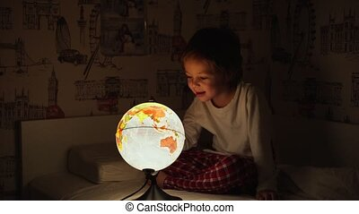 5 year old boy sitting in bed at night rotating the globe and dreams of traveling.
