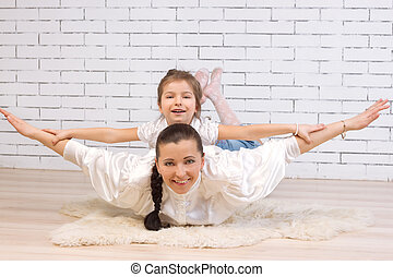 5 year old daughter riding on her mother portrayed flying against the wall