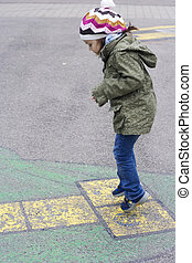 5 years old girl playing a hopscotch