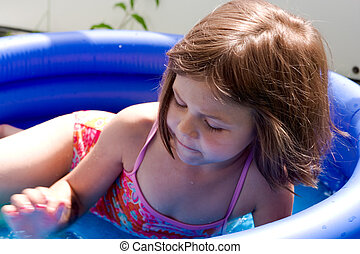 5 years old girl playing in a small swimming pool