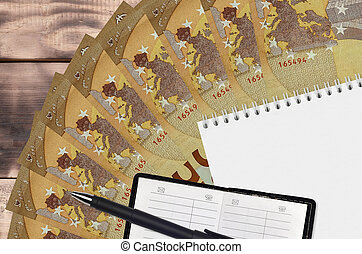 50 euro bills fan and notepad with contact book and black pen. Concept of financial planning and business strategy
