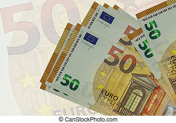 50 euro bills lies in stack on background of big semi-transparent banknote. Abstract presentation of national currency
