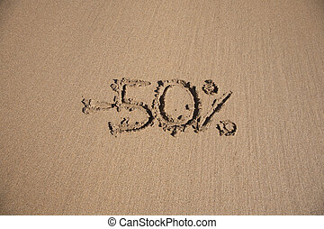 50 percent discount in earth text written on brown sand ...
