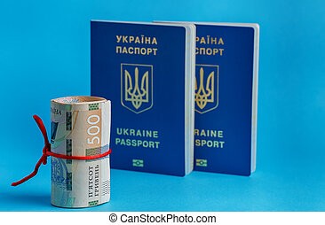 500 hryvnia roll wrapped in a red rope ribbon on the back plate 2 biometric passports of Ukraine on a blue background
