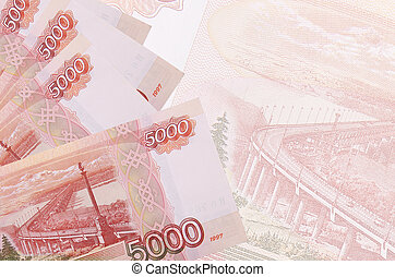 5000 russian rubles bills lies in stack on background of big semi-transparent banknote. Abstract business background