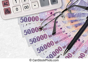 50000 Romanian leu bills fan and calculator with glasses and pen. Business loan or tax payment season concept. Financial planning