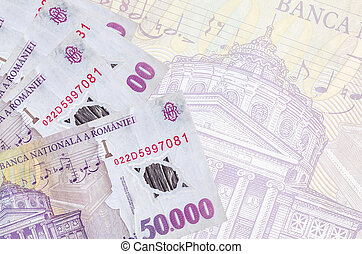 50000 Romanian leu bills lies in stack on background of big semi-transparent banknote. Abstract business background with copy space