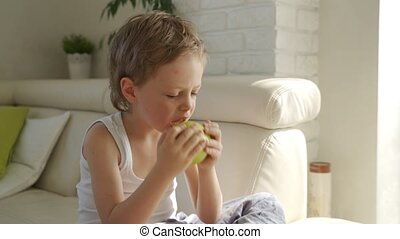6 year old boy eating green apple and try pull out baby...