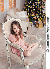 6 years old child girl near Christmas tree with Christmas gifts.