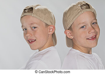 6 years old identical twins wearina a baseball hats smiling