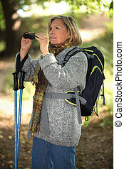 60 years old blonde woman is contemplating landscapes with binoculars, she's wearing warm clothes and using a crook