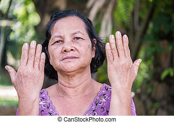 old Thai woman showing her back hand - 60 years old Thai...