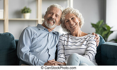 60s loving couple sitting in living room posing looking at ...