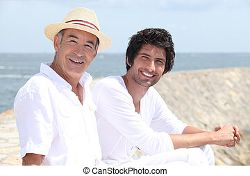 65 years old man and a 30 years old man sitting on the sand with background of sea