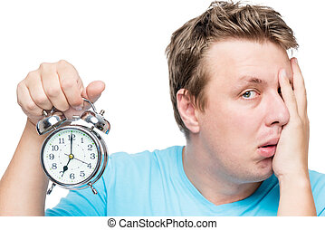 7 am on the alarm clock. A portrait of a sleepy man is isolated