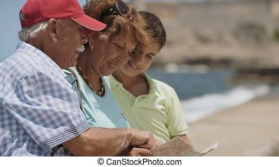 7-Family Grandparents And Boy On Holidays In Cuba Reading Tourist Map