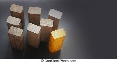 7 same and 1 different wooden blocks standing on black background. Leadership and team abstract business concept