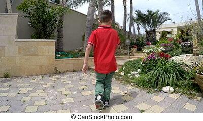 7 years old boy running toward home - Cute young boy playing...
