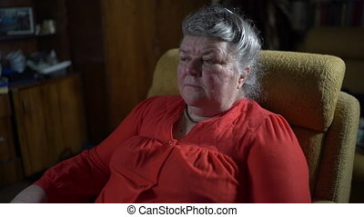 70 year old elderly woman in armchair watching TV