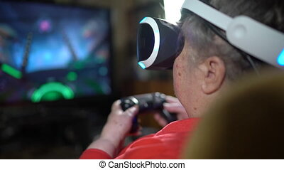 70 year old woman playing video game uses VR headset and...